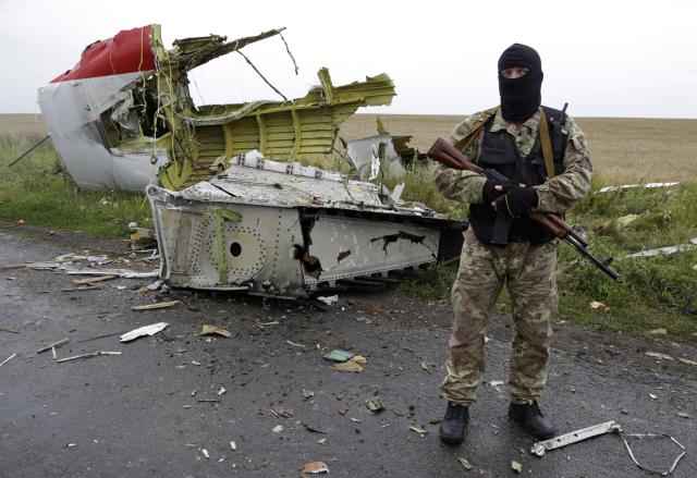 Proruský ozbrojenec poblíž místa katastrofy hlídá trosky letadla před příjezdem pozorovatelů OBSE. (ČTK)