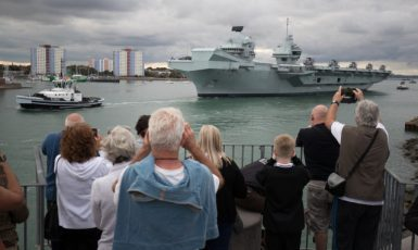 People wave from the Round Tower as the Royal Navy aircraft carrier HMS Queen Elizabeth leaves Portsmouth Naval Base as it sets sail for flight trials. ()