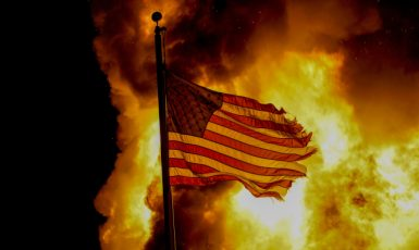 A flag flies over a department of corrections building ablaze during protests, late Monday, Aug. 24, 2020, in Kenosha, Wis., sparked by the shooting of Jacob Blake by a Kenosha Police officer a day earlier. (AP Photo/Morry Gash) ()