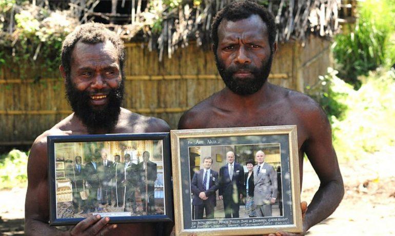Dva příslušníci kmene Yaohnanen ukazují zarámované fotografie z návštěvy prince Philipa, vévody z Edinburghu, v roce 2007. (commons.wikimedia.org/CC BY-SA 3.0, Christopher Hogue Thompson)